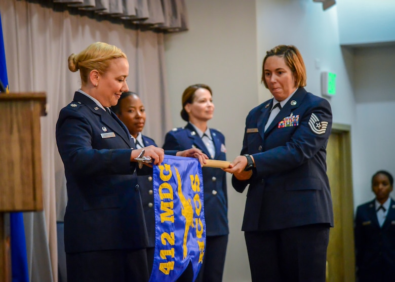 Lt. Col. Jennie Sheffield, the new 412th Health Care Operations Squadron Commander, unfurls the new unit's guidon during an inactivation and redesgination ceremony at Edwards Air Force Base, July 12. The 412th Medical Support Squadron was inactivated its Airmen moved to the 412th Medical Operations Squadron which was then redesignated as the 412th Health Care Operations Squadron. (U.S. Air Force photo by Giancarlo Casem)