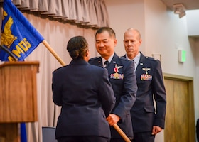 Lt. Col. Vinh Tran, the outgoing 412th Aerospace Medicine Squadron Commander, hands the unit guidon back to Col. Gwendolyn Foster, 412th Medical Group Commander, during an inactivation and redesignation ceremony at Edwards Air Force Base, July 12. Tran relinquished his command to Lt. Col. Arthur Lawrance, the 412th AMDS was then redesignated into the 412th Operational Medical Readiness Squadron.