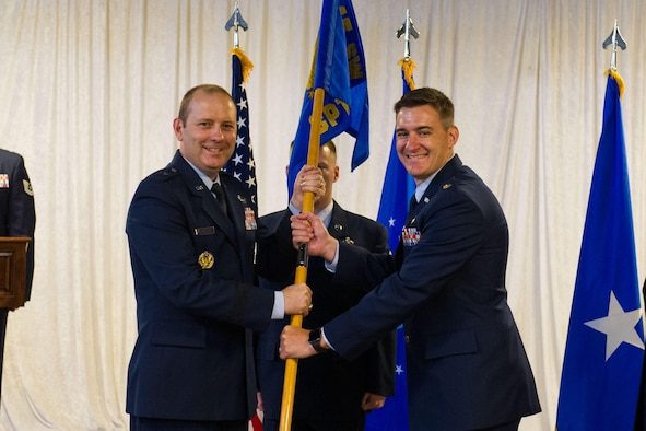 Brig. Gen. Douglas Schiess, 45th Space Wing commander, presents Maj Christopher James, incoming 45th Comptroller Squadron commander, with the 45th CPTS guidon as he assumes command of the squadron. (U.S. Air Force photo by Amanda Ryrholm)