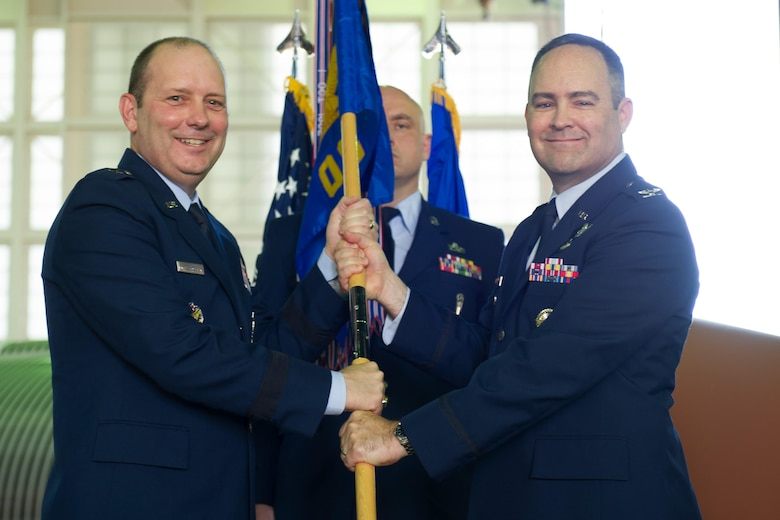 Brig. Gen. Douglas Schiess, 45th Space Wing commander, presents Col. Mark Shoemaker, incoming 45th Operations Group commander, with the 45th OG guidon as he assumes command of the group. (U.S. Air Force photo by Amanda Ryrholm)