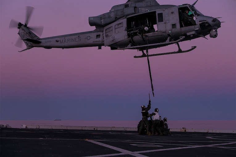 Marines stand below a helicopter during an exercise on a ship.
