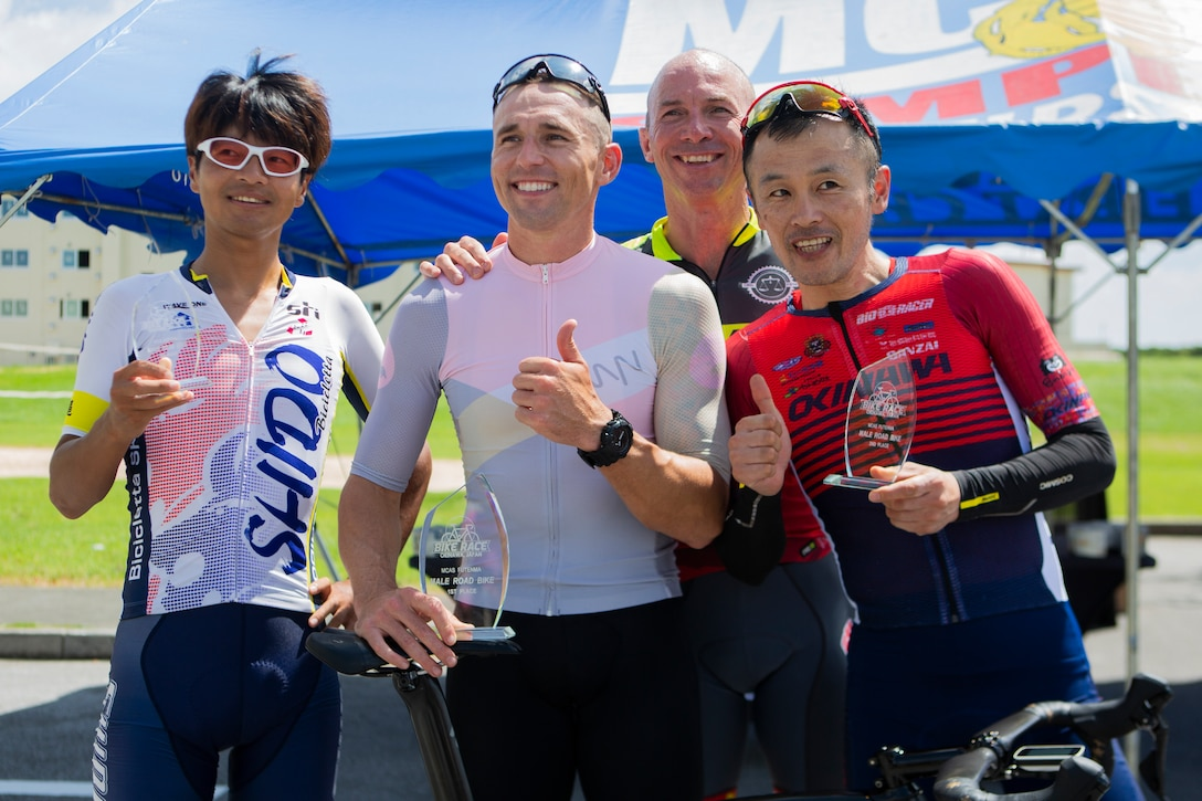 U.S. Marine Corps Col. David Steele, commanding officer of MCAS Futenma, poses for a photo with the top three competitors of the 2019 Futenma Bike Race on Marine Corps Air Station Futenma, Okinawa, Japan, July 14, 2019. The race invites Status of Forces Agreement personnel and the local Okinawan community to compete in race on and around MCAS Futenma's airfield.