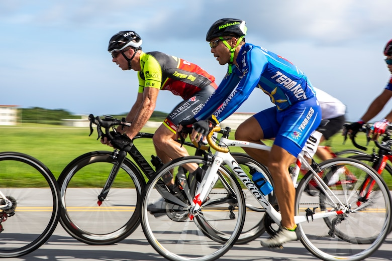 U.S. Marine Corps Col. David Steele, commanding officer of MCAS Futenma, competes to take the lead against a group of local Okinawan cyclists on Marine Corps Air Station Futenma, Okinawa, Japan, July 14, 2019. Cyclists were attending the 2019 Futenma Bike Race; a competition that invites Status of Forces Agreement personnel and the local Okinawan community to compete on and around MCAS Futenma's airfield.
