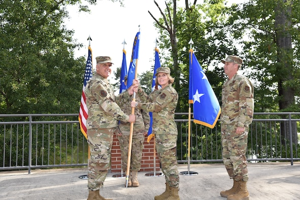 """Maj. Gen. John """"Jay"""" Flournoy Jr. passes the guidon to Brig. Gen. Stacey L. Scarisbrick suring a change of command ceremony on Robins Air Force Base in Georgia on July 15. Scarisbrick takes command of the Air Force Reserve Command Force Generation Center relieving Brig. Gen. Matthew J. Burger. (U.S. Air Force photo by Misuzu Allen)"""