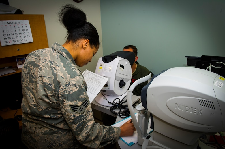 U.S. Air Force Senior Airman Rayne Patton, 926th Aerospace Medicine Squadron optical technician, reads a visual chart to a patient inside the medical clinic, July 13, 2019 at Nellis Air Force Base, Nev. The 926 AMDS provides direct medical support to Reserve Airmen to maintain operational readiness. (U.S. Air Force photo/Senior Airman Brett Clashman)