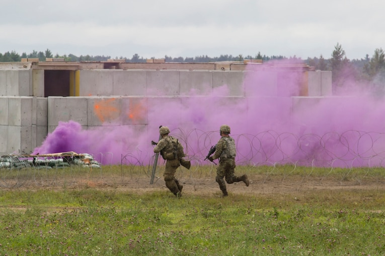 Two soldiers run toward the source of purple smoke during training.