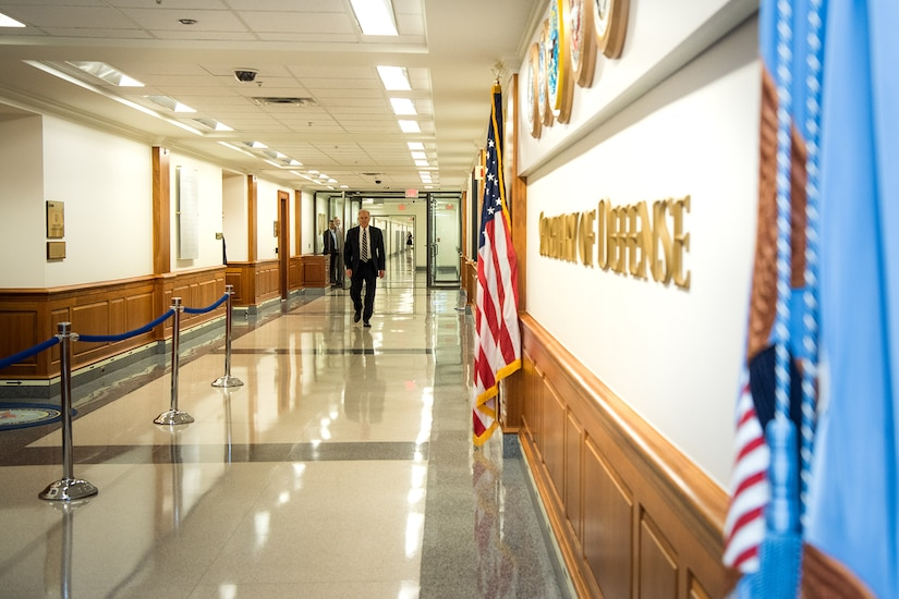 Acting Defense Secretary Richard V. Spencer walks down an empty hallway.