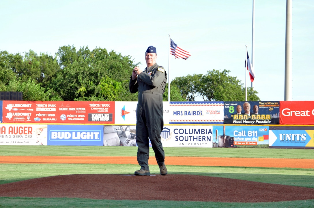 Col. Terry W. McClain, 433rd Airlift Wing commander, throws the first pitch of the game at the San Antonio Missions baseball team's 433rd Airlift Wing Night game July 13, 2019 at Nelson W. Wolff Municipal Stadium.