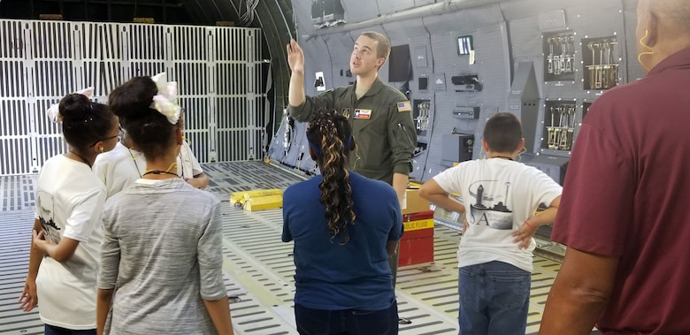 Tech. Sgt. Joshua Green, 356th Airlift Squadron loadmaster, describes the C-5M Super Galaxy's cargo compartment to students with the San Antonio Chapter of Tuskegee Airmen Inc.'s Youth Science, Technology, Engineering and Mathematics-Aviation Program July 12, 2019 at Joint Base San Antonio-Lackland, Texas.