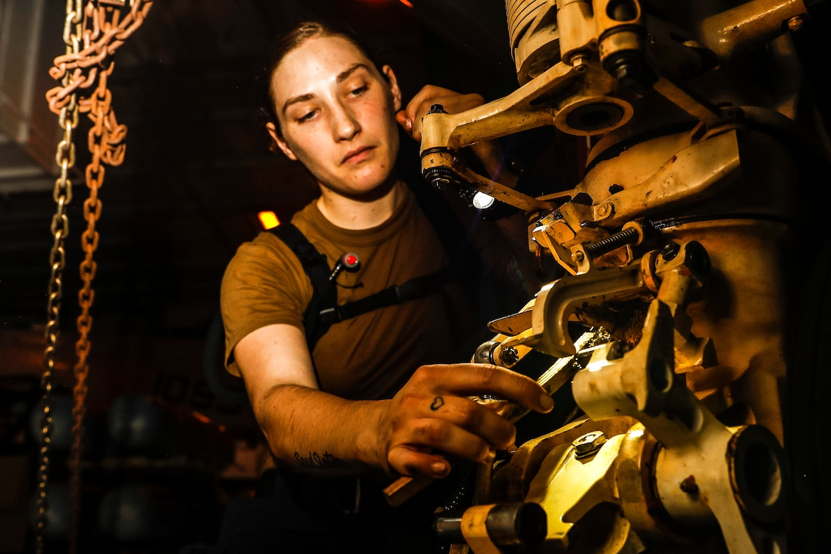 A sailor removes corrosion from an aircraft part.