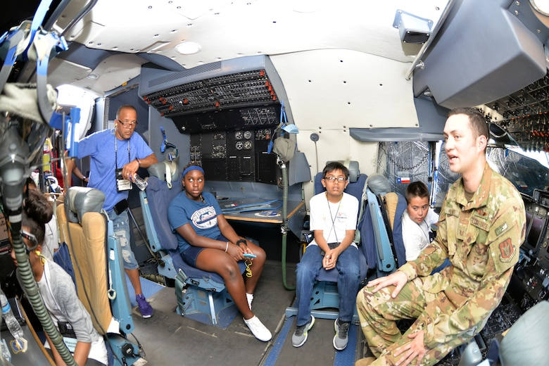 Tech. Sgt. Jason Henry, 356th Airlift Squadron flight engineer, talks to students with the San Antonio Chapter of Tuskegee Airmen Inc.'s Youth Science, Technology, Engineering and Mathematics-Aviation Program about the C-5M Super Galaxy's flight deck July 12, 2019 at Joint Base San Antonio-Lackland, Texas.