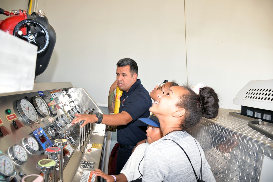 Mike Vigil, 802nd Civil Engineer Squadron firefighter, explains the controls for a fire engine to students with the San Antonio Chapter of Tuskegee Airmen Inc.'s Youth Science, Technology, Engineering and Mathematics-Aviation Program during a tour of Fire Station #1 July 12, 2019 at Joint Base San Antonio-Lackland, Texas.