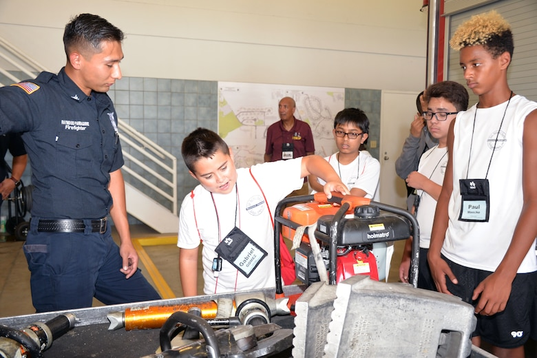 Raymundo Parraguirre, 802nd Civil Engineer Squadron firefighter, talks with students with the San Antonio Chapter of Tuskegee Airmen Inc.'s Youth Science, Technology, Engineering and Mathematics-Aviation Program about firefighter tools during a tour of Fire Station #1 July 12, 2019 at Joint Base San Antonio-Lackland, Texas.