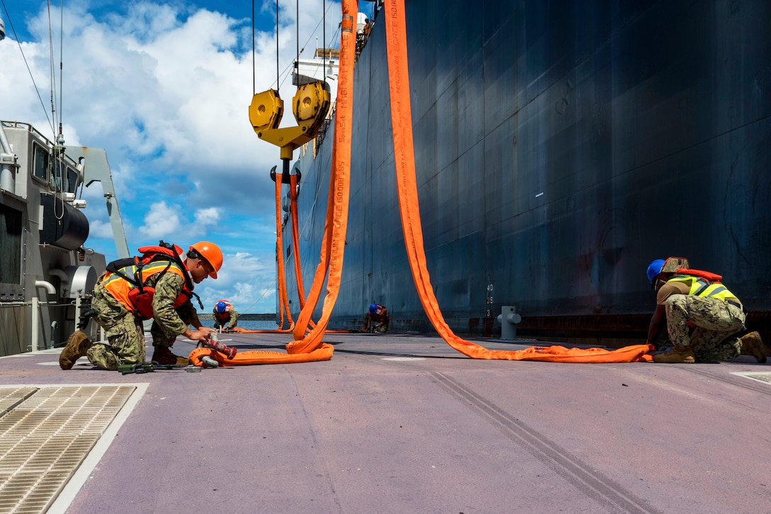 Several sailors attach orange lines near a ship.