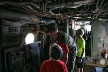 U.S. Marine Corps Lance Cpl. Cole Bensenhaver, an avionics technician with Marine Medium Tiltrotor Squadron 268 (VMM-268), gives a tour of an Osprey at the VMM-268 squadron, Marine Corps Air Station Kaneohe Bay, June 12, 2019. The one-day camp program, hosted by the Armed Services YMCA, serves military children as an outlet for youth to share their common experiences and receive academic, recreational and leadership-based enrichment. (U.S. Marine Corps photo by Pfc. Samantha Sanchez)