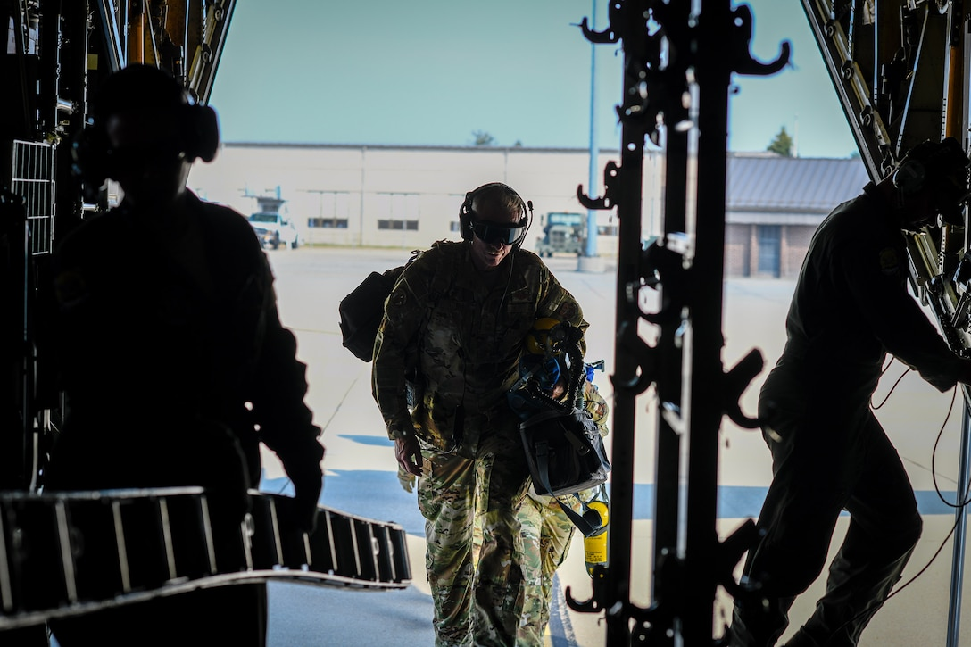A reserve Airman with the 445th Aeromedical Evacuation Squadron walks aboard a Youngstown Air Reserve Station C-130H Hercules on the flight line at Wright-Patterson Air Force Base, Ohio, July 10, 2019. YARS personnel flew to Wright-Patterson AFB to provide airlift an aeromedical evacuation training sortie. (U.S. Air Force photo by Senior Airman Christina Russo)
