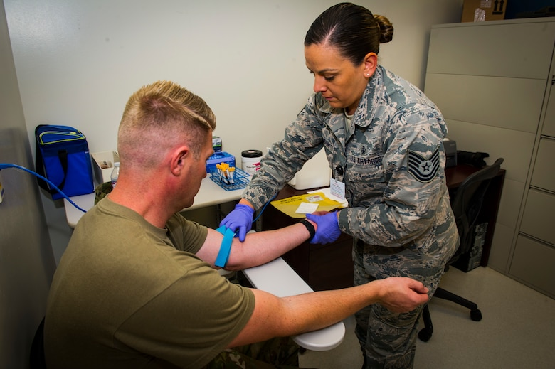 U.S. Air Force Tech Sgt. Leslie Robinson, 926th Aerospace Medicine Squadron medical lab technician, preps Master Sgt. Nicholas Hicks, 926th Aircraft Maintenance Squadron viper aircraft maintenance unit flight chief, to have blood drawn inside the medical clinic at Nellis Air Force Base, Nevada, July 13, 2019. The 926th AMDS provides flight medical support and medical manpower to accomplish the Reserve Component Physical Health Assessment Process for the wing population to ensure units' medical requirements for deployment are met.. The 926 AMDS works cohesively to ensure all reserve personnel assigned are medically and operationally ready to fulfill the wing's mission. (U.S. Air Force photo by Senior Airman Brett Clashman)