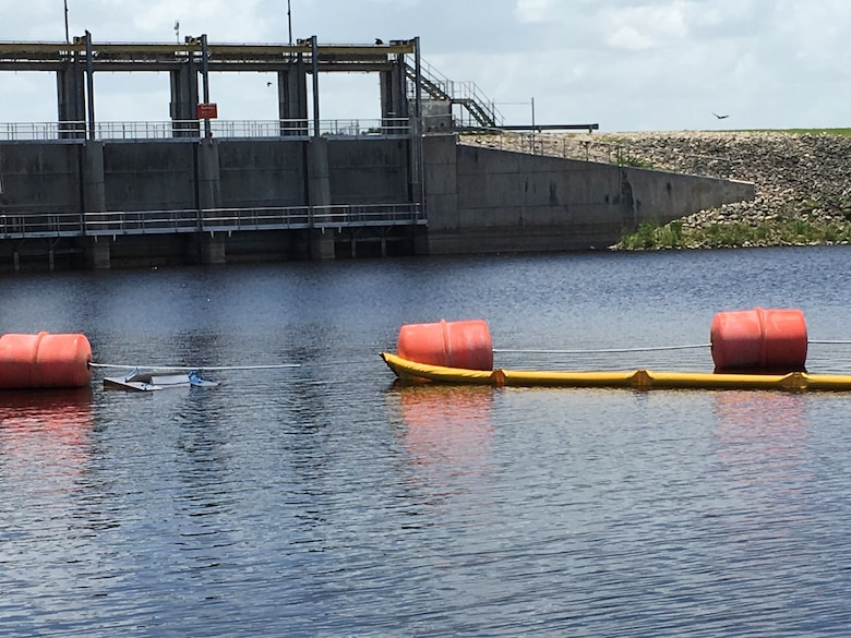 Floating weir skimmer and boom for focusing and collecting algae from water upstream of Moore Haven spillway.