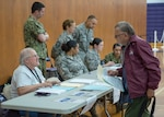 Patient administrators with the Greater Chenango Care Innovative Readiness Training check-in patients July 15, 2019, at Norwich High School, Norwich, New York. IRT is a Department of Defense hands-on military training opportunity that delivers joint training opportunities to increase deployment readiness while providing key services for our American communities.