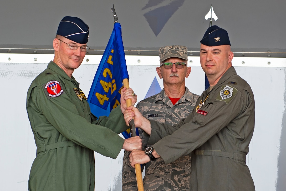 Brig. Gen. Rogers Suro, left, 442d Fighter Wing commander, receives the guidon from Col. Gerald Cook, 476th Fighter Group (FG) commander, right, as he relinquishes command during the 476th FG change of command ceremony, July 9, 2019, at Moody Air Force Base (AFB), Ga. Cook is a command pilot with more than 3,200 flying hours. (U.S. Air Force photo by Airman Azaria E. Foster)