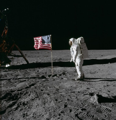 "Astronaut Edwin E. Aldrin Jr., lunar module pilot of the first lunar landing mission, poses for a photograph beside the deployed United States flag during an Apollo 11 extravehicular activity (EVA) on the lunar surface. The Lunar Module (LM) is on the left, and the footprints of the astronauts are clearly visible in the soil of the moon. Astronaut Neil A. Armstrong, commander, took this picture with a 70mm Hasselblad lunar surface camera. While astronauts Armstrong and Aldrin descended in the LM, the ""Eagle"", to explore the Sea of Tranquility region of the moon, astronaut Michael Collins, command module pilot, remained with the Command and Service Modules (CSM) ""Columbia"" in lunar orbit. Photo credit: NASA"