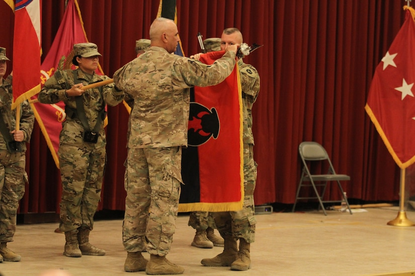 Major Gen. Ben Corell, left, commanding general, and Command Sgt. Maj. Joseph Hjelmstad, senior enlisted leader, 34th Red Bull Infantry Division, Minnesota Army National Guard, prepare to case the unit colors to signify the end of its run as the Task Force Spartan headquarters element during a transfer of authority ceremony at Camp Arifjan, Kuwait, July 15, 2019. The Red Bull Division handed authority to the 38th Infantry Division, Indiana Army National Guard after serving as the TFS division headquarters from November 2018 to July 2019.