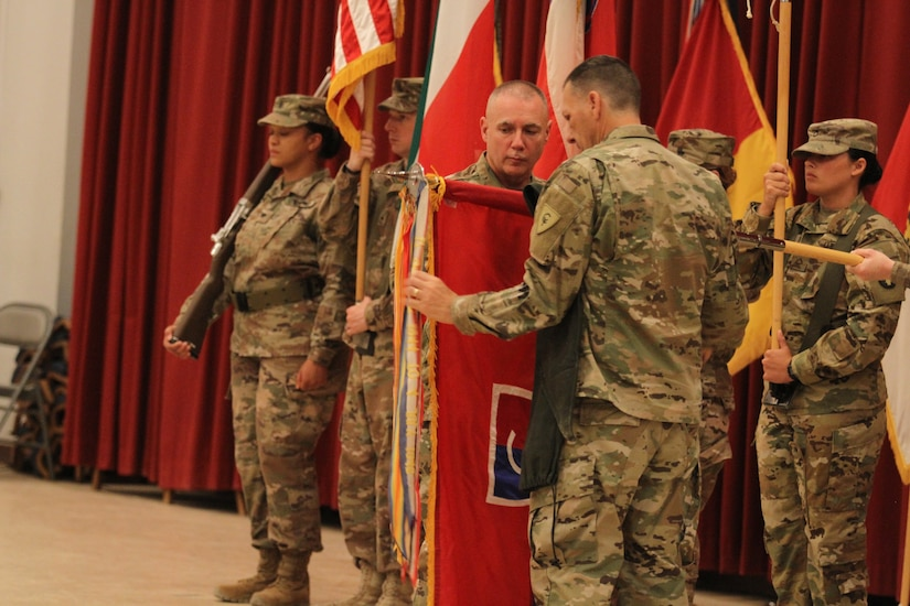 Major Gen. Gordon Ellis, left, commanding general, and Command Sgt. Maj. Dale Shetler, senior enlisted leader, 38th Infantry Division, Indiana Army National Guard, uncase the division colors to symbolize the transfer of authority as the Task Force Spartan division headquarters element during a ceremony at Camp Arifjan, Kuwait, July 15, 2019. Task Force Spartan serves to increase military readiness and capability in order to maintain regional stability and expand regional partnerships in the U.S. Central Command's area of responsibility.
