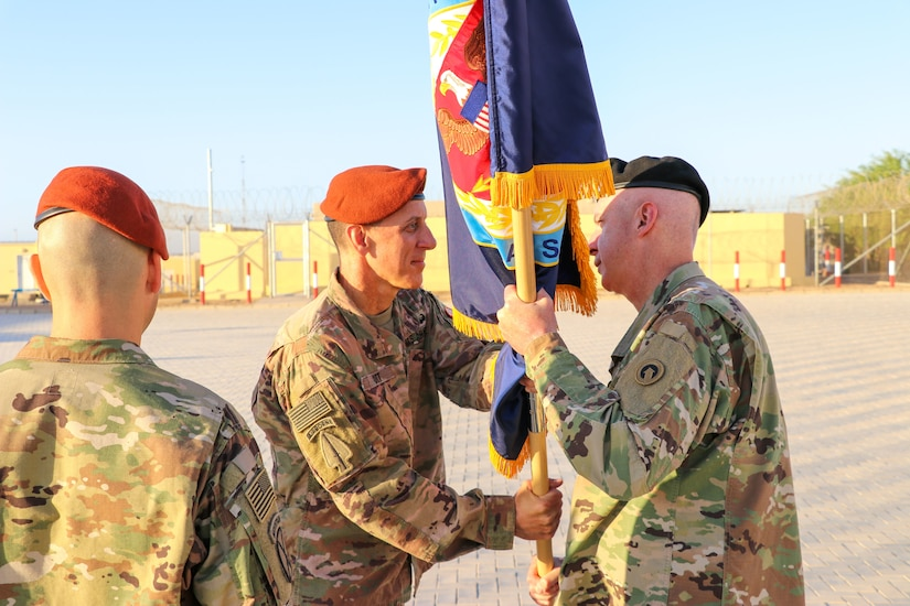 U.S. Army Col. Mark P. Ott, the outgoing commander of Task Force Sinai (TFS), passes the TFS colors to Maj. Gen. John P. Sullivan, commander of the 1st Theater Sustainment Command, during a change of command ceremony at South Camp, Egypt, July 15, 2019.