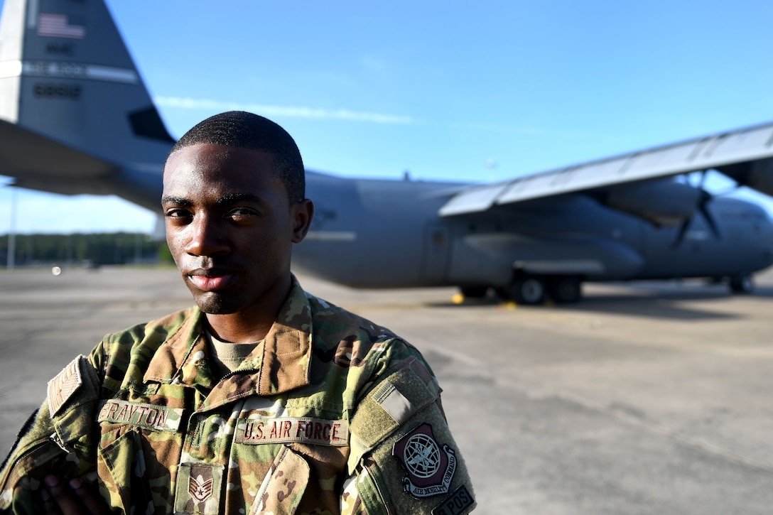 A man stands in front of a C-130J.