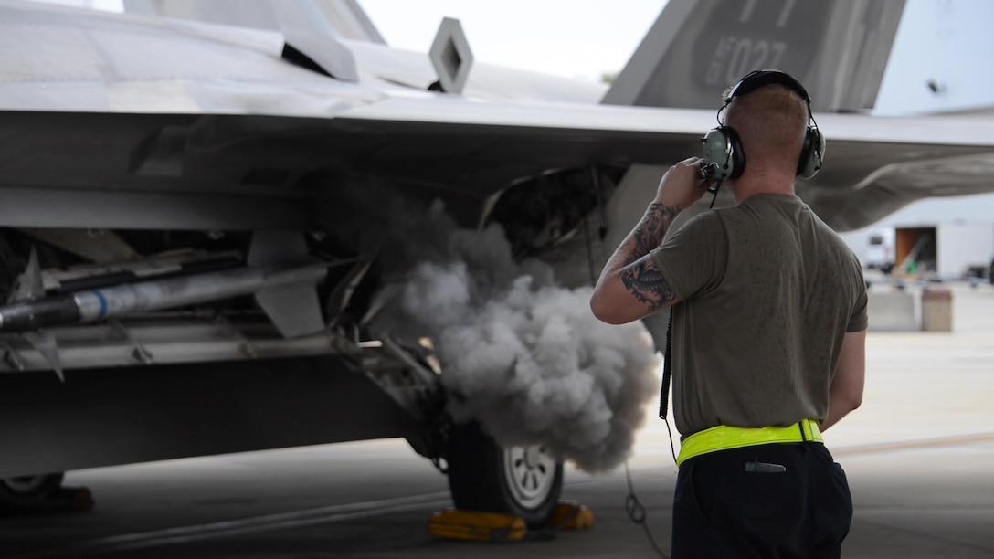 U.S. Air Force Senior Airman Jordan Arnold, 325th Aircraft Maintenance Squadron crew chief, from Tyndall Air Force Base, monitors an F-22 Raptor turning on at Eglin AFB, Florida, July 2, 2019.
