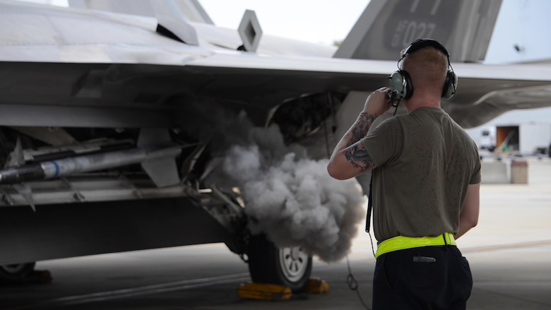 U.S. Air Force Senior Airman Jordan Arnold, 325th Aircraft Maintenance Squadron crew chief, from Tyndall Air Force Base, monitors an F-22 Raptor turning on at Eglin AFB, Florida, July 2, 2019.