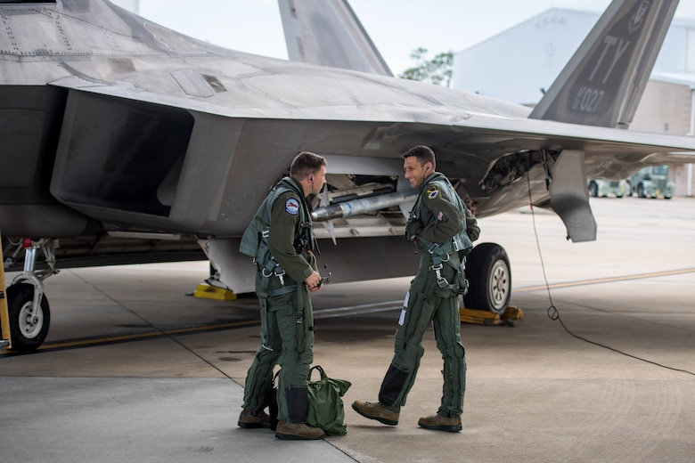 A U.S. Air Force F-22 Raptor pilot, 43rd Fighter Squadron from Tyndall Air Force Base, briefs the next pilot to fly the aircraft after hot pit refueling at Eglin AFB, Florida, July 2, 2019.