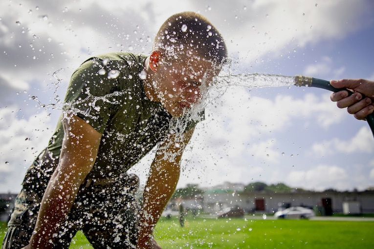 A sailor gets sprayed in the face with water from a person holding a water hose.