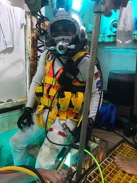 David Coan, extra vehicular activity lead for the National Aeronautics and Space Administration (NASA) Johnson Space Center prepares for a dive donning a Kirby Morgan-37 helmet equipped with the Divers Augmented Vision Device Generation 1.0 heads-up display during the 23rd NASA Extreme Environment Mission Operations in June 2019 at the Aquarius Reef Base underwater habitat.