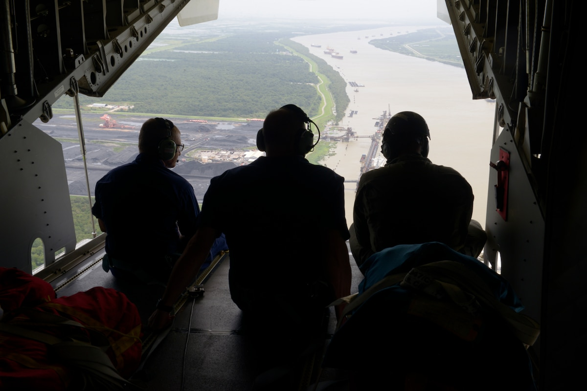 Three men look out from a helicopter at a flooded river.