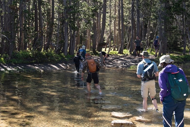 U.S. Air Force Airmen from Travis Air Force Base, California, cross a river during a resilience hike July 13, 2019, Yosemite National Park, California. The Airmen hiked to Cloud's Rest covering 14.57 miles as they climbed to 9,926 feet above sea level. The hike was organized to enhance the Airmen's physical, mental and spiritual resiliency. (U.S. Air Fore photo by Tech. Sgt. James Hodgman)