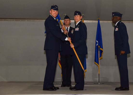 The 57th Wing commander passes the guide on to the new 57th Adversary Tactics Group commander.