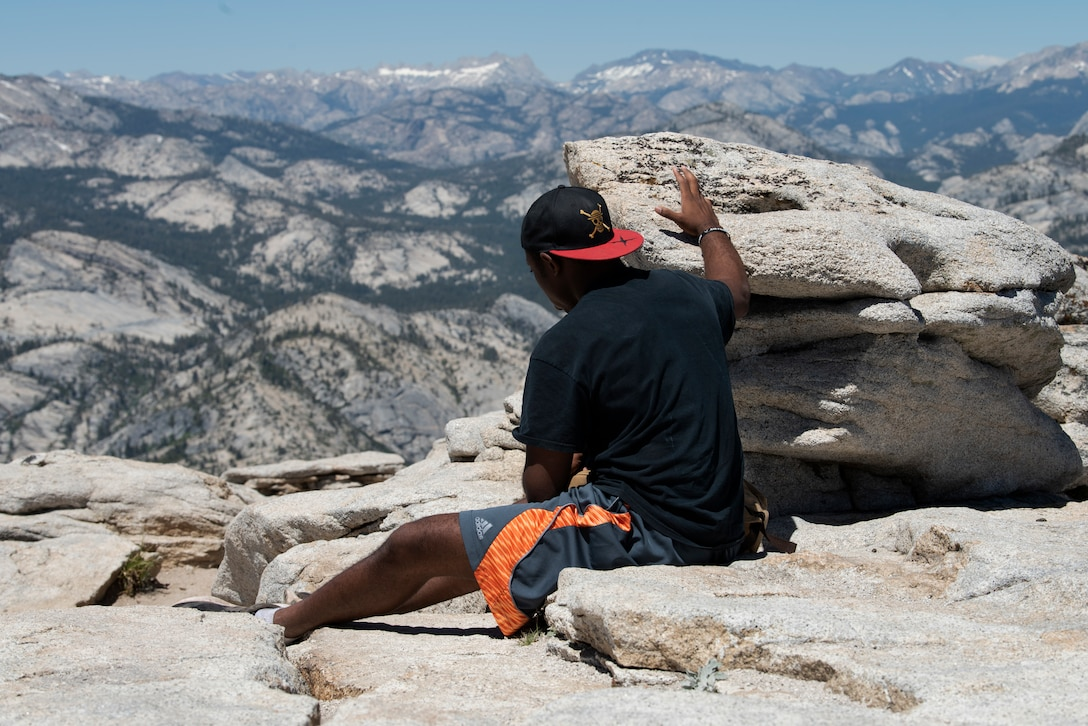 U.S. Air Force Capt. Ayodeji Alaketu, 60th Medical Operations Squadron family resident physician, enjoys the view from the summit of Cloud's Rest July 13, 2019, at Yosemite National Park, California. Alaketu and 41 other Airmen from Travis Air Force Base, California, hiked to Cloud's Rest covering 14.57 miles as they climbed to 9,926 feet above sea level. The hike was organized to enhance the Airmen's physical, mental and spiritual resiliency. (U.S. Air Fore photo by Tech. Sgt. James Hodgman)