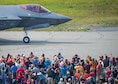 "Airshow spectators wave as Capt. Andrew ""Dojo"" Olson, F-35 Demonstration Team pilot and commander returns from performing an aerial demonstration during the Arctic Lightning Airshow July 13, 2019, at Eielson Air Force Base, Alaska. Spectators got an up-close look at the Air Force's newest fighter jet marking the airshow since 2008. (U.S. Air Force photo by Senior Airman Alexander Cook)"