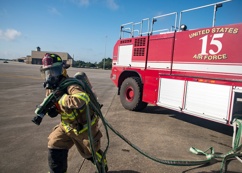 A firefighter from the 23d Civil Engineer Squadron (CES), pulls a hose during HC-130J Combat King II egress training, July 11, 2019, at Moody Air Force Base, Ga. Firefighters conducted the training to evaluate their overall knowledge and proficiency of how to properly shut down and rescue personnel from a C-130 during an emergency situation. (U.S. Air Force photo by Airman 1st Class Eugene Oliver)