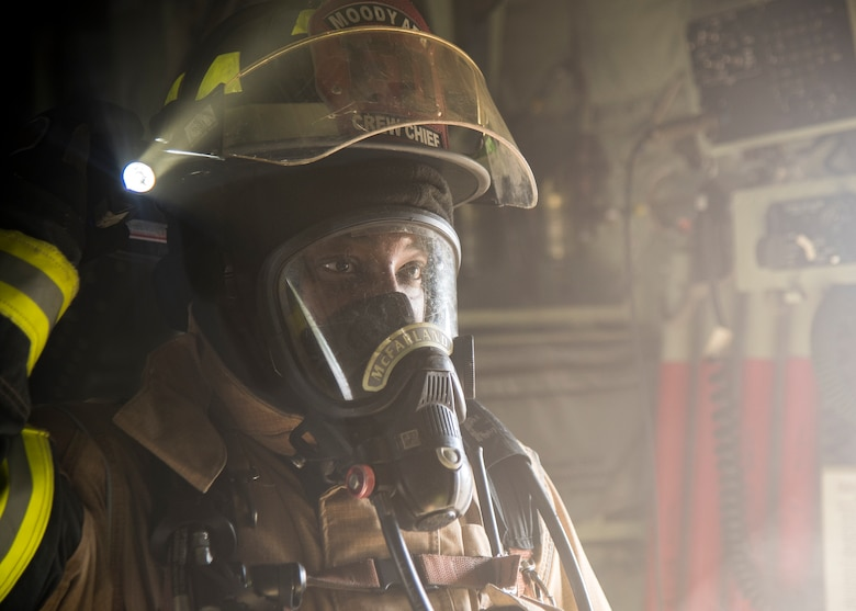 Staff Sgt. Tyler McFarland, 23d Civil Engineer Squadron (CES) firefighter crew chief, searches for personnel to rescue during HC-130J Combat King II egress training, July 11, 2019, at Moody Air Force Base, Ga. Firefighters conducted the training to evaluate their overall knowledge and proficiency of how to properly shut down and rescue personnel from a C-130 during an emergency situation. The training required the firefighters to properly enter and ventilate the aircraft while conducting swift rescue techniques to safely locate and remove passengers from the aircraft. (U.S. Air Force photo by Airman 1st Class Eugene Oliver)