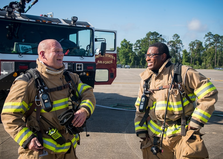 Tech Sgt Gary Schmidt, left, 23d Civil Engineer Squadron (CES) firefighter station chief and Staff Sgt. Tyler McFarland, 23d CES firefighter crew chief, share a laugh following HC-130J Combat King II egress training, July 11, 2019, at Moody Air Force Base, Ga Firefighters conducted the training to evaluate their overall knowledge and proficiency of how to properly shut down and rescue personnel from a C-130 during an emergency situation. The training required the firefighters to properly enter and ventilate the aircraft while conducting swift rescue techniques to safely locate and remove passengers from the aircraft. (U.S. Air Force photo by Airman 1st Class Eugene Oliver)