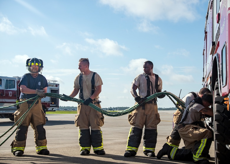 Firefighters from the 23d Civil Engineer Squadron (CES), put up a hose following HC-130J Combat King II egress training, July 11, 2019, at Moody Air Force Base, Ga. Firefighters conducted the training to evaluate their overall knowledge and proficiency of how to properly shut down and rescue personnel from a C-130 during an emergency situation. The training required the firefighters to properly enter and ventilate the aircraft while conducting swift rescue techniques to safely locate and remove passengers from the aircraft. (U.S. Air Force photo by Airman 1st Class Eugene Oliver)