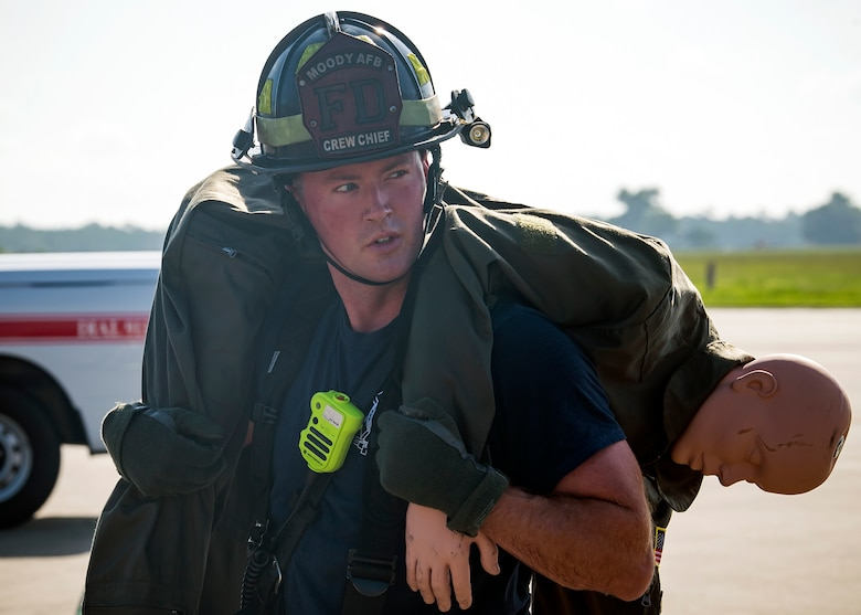 Donald Carey, 23d Civil Engineer Squadron (CES) crew chief, carries a simulated aircrew member during HC-130J Combat King II egress training, July 11, 2019, at Moody Air Force Base, Ga. Firefighters conducted the training to evaluate their overall knowledge and proficiency of how to properly shut down and rescue personnel from a C-130 during an emergency situation. The training required the firefighters to properly enter and ventilate the aircraft while conducting swift rescue techniques to safely locate and remove passengers from the aircraft. (U.S. Air Force photo by Airman 1st Class Eugene Oliver)
