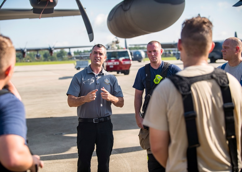 Stacey Maples, center, 23d Civil Engineer Squadron (CES) assistant fire chief, discusses the performance of the firefighters from the 23d CES following HC-130J Combat King II egress training, July 11, 2019, at Moody Air Force Base, Ga. Firefighters conducted the training to evaluate their overall knowledge and proficiency of how to properly shut down and rescue personnel from a C-130 during an emergency situation. The training required the firefighters to properly enter and ventilate the aircraft while conducting swift rescue techniques to safely locate and remove passengers from the aircraft. (U.S. Air Force photo by Airman 1st Class Eugene Oliver)