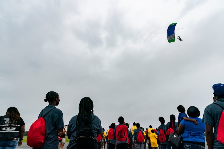 Participants watch a skydiver during the Eyes Above the Horizon diversity outreach program, July 13, 2019, in Valdosta, Ga. The Valdosta Regional Airport hosted the Legacy Flight Academy and over 60 youths ranging in age from 10-19 for a day of flight introduction and immersion into the legacy of the historic Tuskegee Airmen. The program is designed to remove barriers for underrepresented minorities and inspire an interest in aerospace careers. (U.S. Air Force photo by Airman 1st Class Hayden Legg)