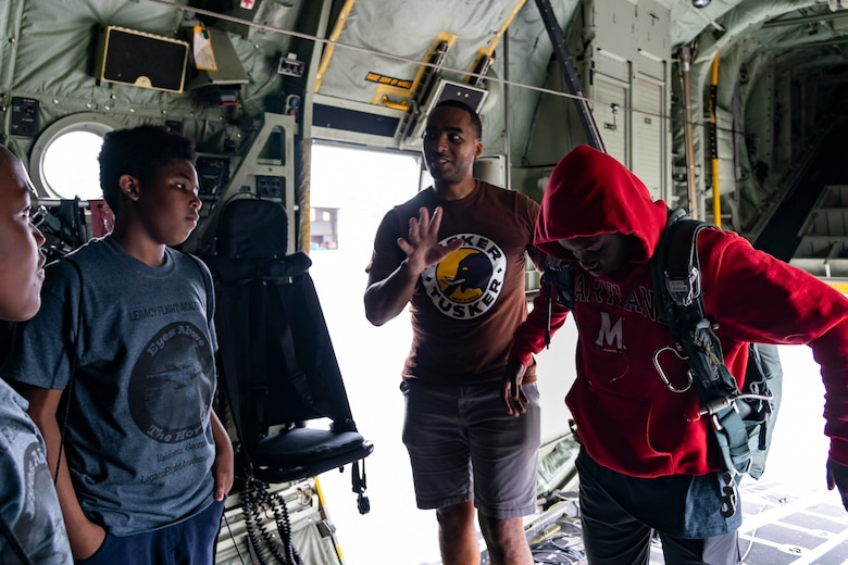 A participant tries on a parachute during the Eyes Above the Horizon diversity outreach program, July 13, 2019, in Valdosta, Ga. The Valdosta Regional Airport hosted the Legacy Flight Academy and over 60 youths ranging in age from 10-19 for a day of flight introduction and immersion into the legacy of the historic Tuskegee Airmen. The program is designed to remove barriers for underrepresented minorities and inspire an interest in aerospace careers. (U.S. Air Force photo by Airman 1st Class Hayden Legg)