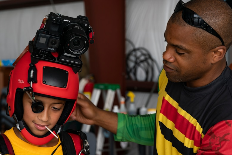 Nicholas Walker, right, Team Blackstar Skydivers Demonstration Team member, puts his helmet on a participant during the Eyes Above the Horizon diversity outreach program, July 13, 2019, in Valdosta, Ga. The Valdosta Regional Airport hosted the Legacy Flight Academy and over 60 youths ranging in age from 10-19 for a day of flight introduction and immersion into the legacy of the historic Tuskegee Airmen. The program is designed to remove barriers for underrepresented minorities and inspire an interest in aerospace careers. (U.S. Air Force photo by Airman 1st Class Hayden Legg)