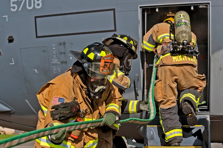 Firefighters from the 23d Civil Engineering Squadron (CES) carry a hose during an HC-130J Combat King II egress training, July 11, 2019, on Moody Air Force Base, Ga. The 23d CES conducted the exercise to simulate the rescue of victims from a smoking C-130. The firefighters were tasked with locating and providing ventilation within the aircraft to safely remove the victims. (U.S. Air Force photo by Airman Azaria E. Foster)