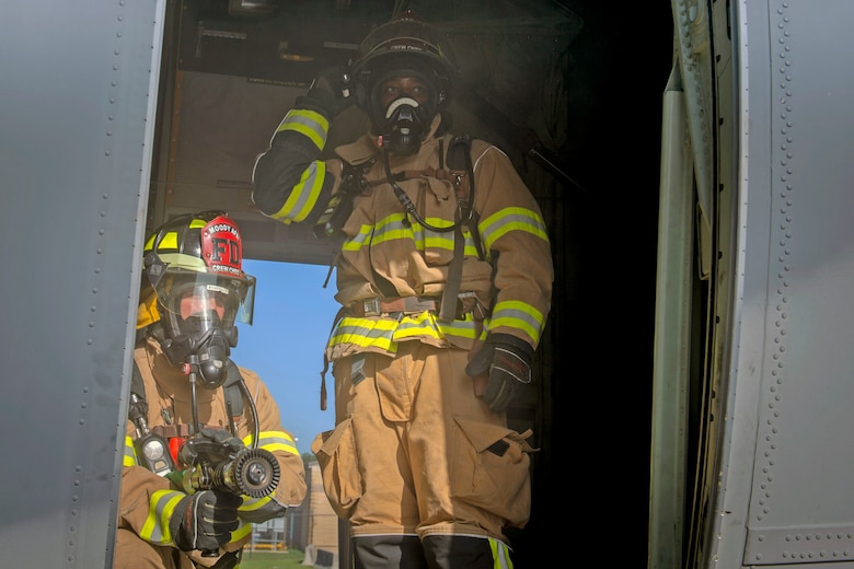 Staff Sgt. Matthew Montville, left, and Staff Sgt. Tyler McFarland, right, both 23d Civil Engineering Squadron firefighter crew chiefs, hold their position during an HC-130J Combat King II egress training, July 11, 2019, on Moody Air Force Base, Ga. The 23d CES conducted the exercise to simulate the rescue of victims from a smoking C-130. The firefighters were tasked with locating and providing ventilation within the aircraft to safely remove the victims. (U.S. Air Force photo by Airman Azaria E. Foster)